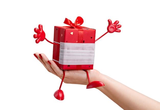 Presente em caixa em papel vermelho e máscara protetora na mão feminina. nós derrotamos o vírus.