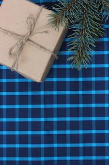 Presente em papel comum e um galho de abeto em um fundo quadriculado azul, vista superior. textura de férias de natal ou ano novo. colocação plana. copie o espaço.