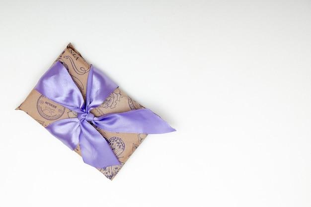 Presente em um fundo branco com papel marrom de laço de fita lilás