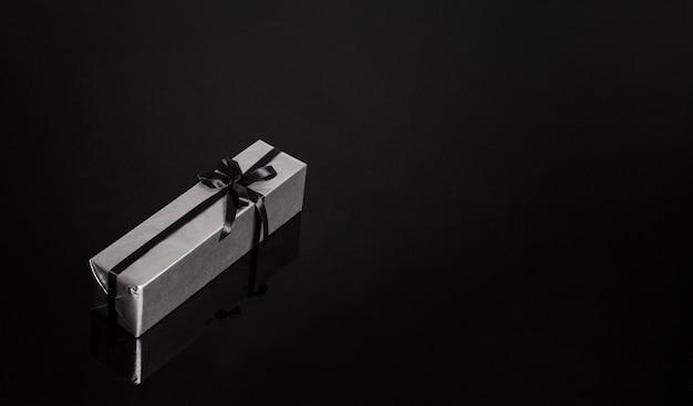 Presente em um pacote prateado com uma fita preta