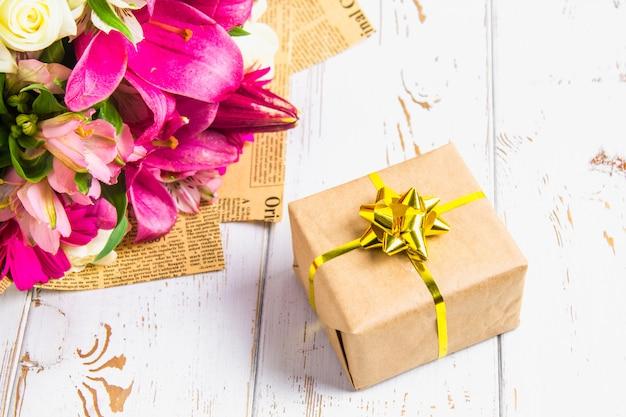 Presente em uma caixa e um buquê de flores em uma mesa de madeira branca. festa de aniversário