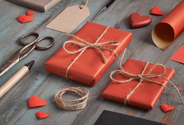 Presente embalado, papel de embrulho, etiquetas e decorações na mesa de madeira rústica