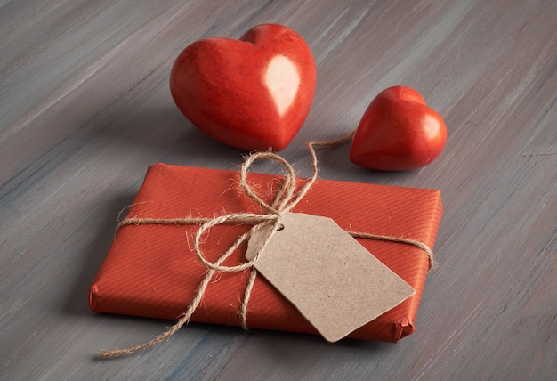 Presente embrulhado com tag de papel em branco e dois corações de pedra vermelha