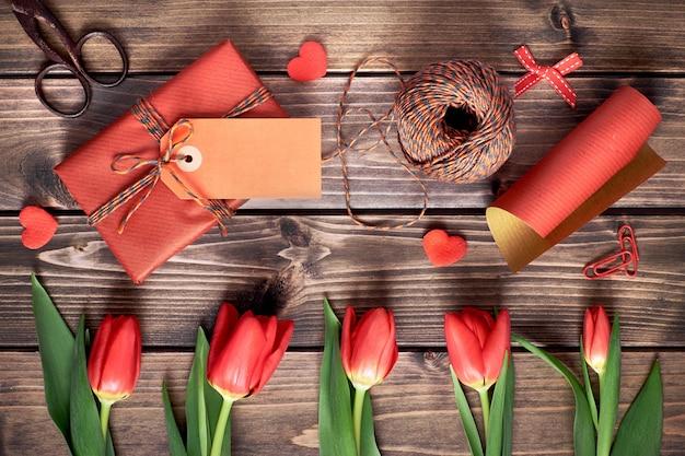 Presente embrulhado com tag, plana leigos com tulipas laranja, papel de embrulho e cordão