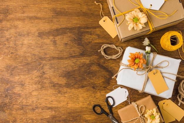 Presente embrulhado com tag vazia e bela flor sobre a mesa de madeira