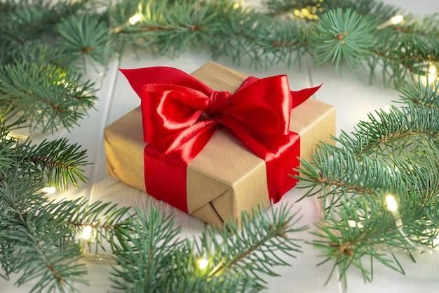 Presente embrulhado em papel artesanal e fita vermelha com galhos verdes de uma árvore de natal com guirlanda de lâmpadas led