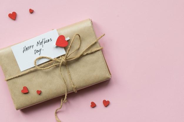 Presente embrulhado em papel artesanal marrom e amarre a corda de cânhamo. caixa de presente com saudações no dia das mães. vista do topo.