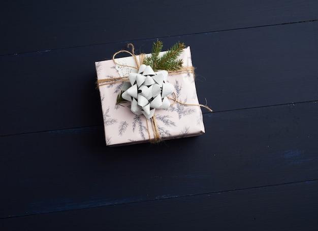 Presente embrulhado em papel colorido sobre uma superfície de madeira azul