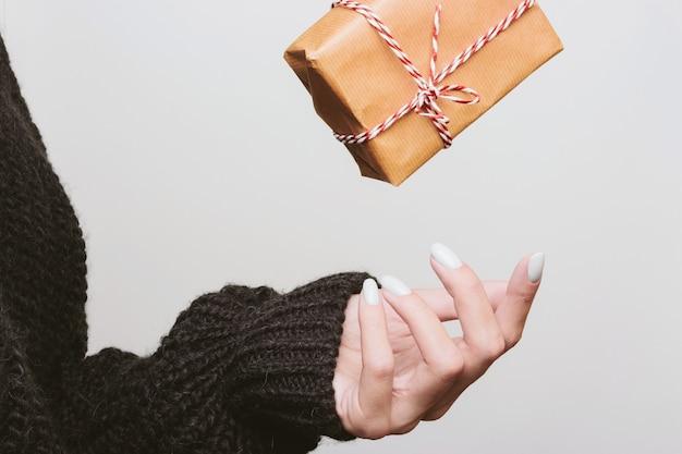 Presente embrulhado em papel kraft cai nas mãos de uma menina. atire uma caixa
