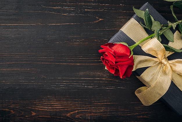 Presente embrulhado em papel preto e uma fita de ouro. no topo da caixa está uma luxuosa rosa vermelha.