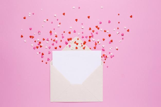 Presente envelope e cartão com corações rosa e vermelhas em rosa