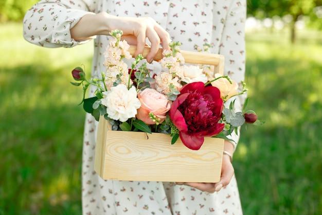 Presente feito à mão feito de rosas de pêssego, peônias, rosas vermelhas, embaladas em uma caixa de madeira.
