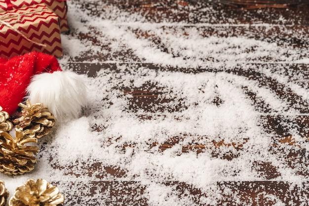 Presente festivo com laço close-up em fundo de madeira com neve