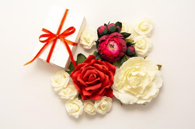 Presente, fita vermelha, flores vermelhas e brancas vista superior