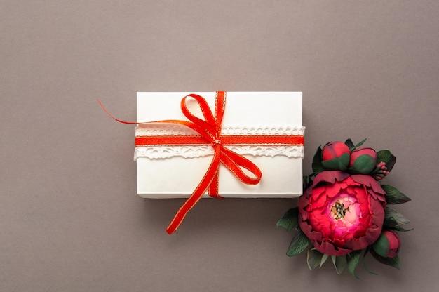 Presente, fita vermelha, rosa flores vista superior