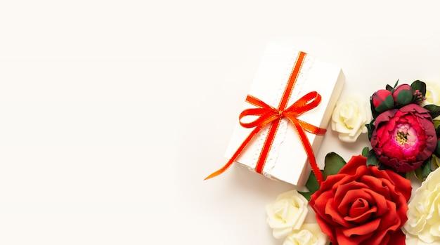 Presente, fita vermelha, vista superior de flores vermelhas