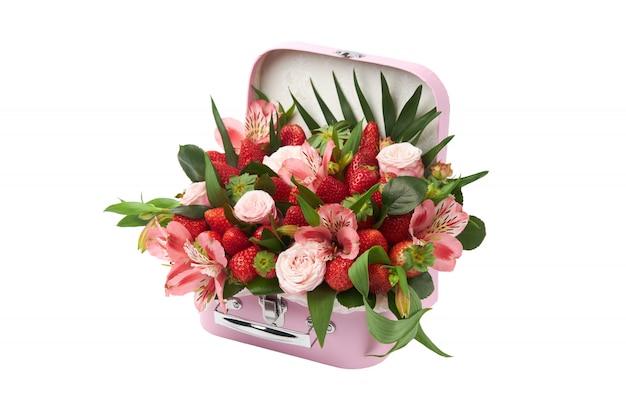 Presente incomum na forma de uma mala rosa cheia de rosas, orquídeas e morangos maduros em um fundo branco