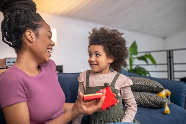 Presente interessante. rindo alegre mãe afro-americana com pálpebras caídas com a caixa aberta e olhando a filhinha sorridente sentada no sofá