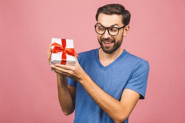 Presente maravilhoso! foto adorável de homem atraente com sorriso lindo, segurando sua caixa de presente de aniversário