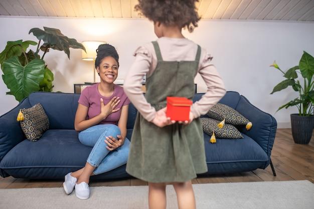 Presente. menina segurando um presente em uma caixa vermelha nas costas para uma mãe sorridente com penteado alto, sentada no sofá em uma sala iluminada