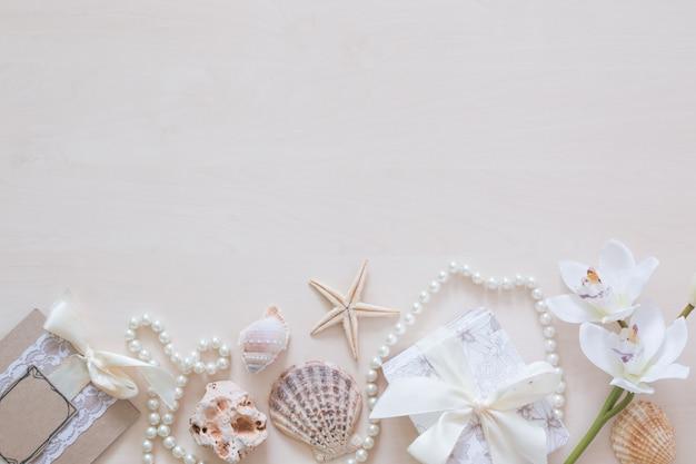 Presente, miçangas, conchas, orquídea e copyspace
