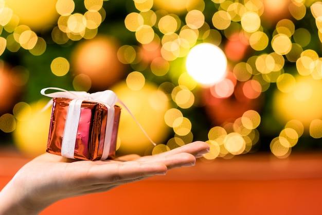 Presente na mão com luz de fundo de bokeh de natal