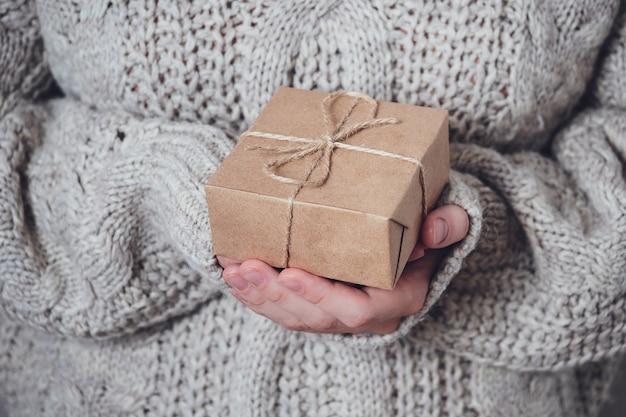 Presente nas mãos das mulheres, close-up. conceito de presente monocromático e minimalista. uma garota com um suéter segura uma caixa de presente feita de papel kraft, amarrada com um barbante. fundo surpresa.
