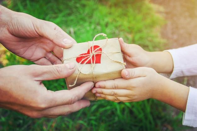 Presente nas mãos de uma criança. parabéns pelo dia de seu pai.