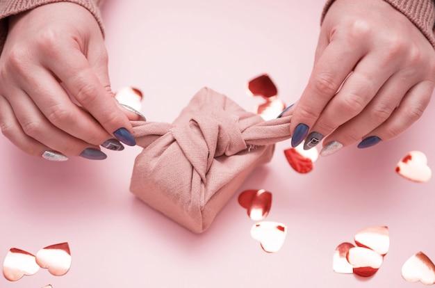 Presente nas mãos femininas com uma bela manicure. presente em embalagem ecológica - furoshiki.