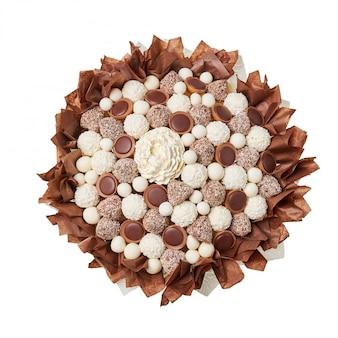 Presente original na forma de um buquê composto por chocolates brancos e marrons sobre fundo branco, vista superior
