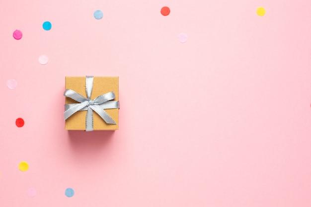 Presente ou caixa atual e confetes da cor na tabela cor-de-rosa com espaço para o texto.