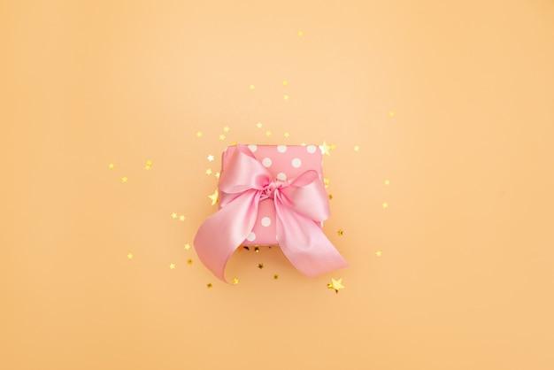 Presente ou caixa atual e confetes das estrelas na opinião de tampo da mesa cor-de-rosa. composição plana leiga para aniversário, dia das mães ou casamento.