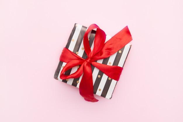 Presente ou caixa atual nas listras brancas e pretas com uma curva vermelha da fita isolada na opinião de tampo da mesa cor-de-rosa.