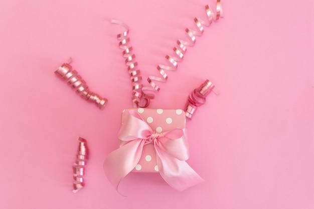 Presente ou caixa presente e confetes de estrelas na vista superior de mesa-de-rosa