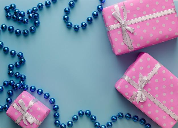 Presente ou caixas de presente rosa com fita sobre fundo azul pastel