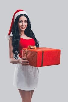 Presente para você! mulher jovem e atraente com chapéu de papai noel segurando uma caixa de presente vermelha e sorrindo em frente ao fundo cinza