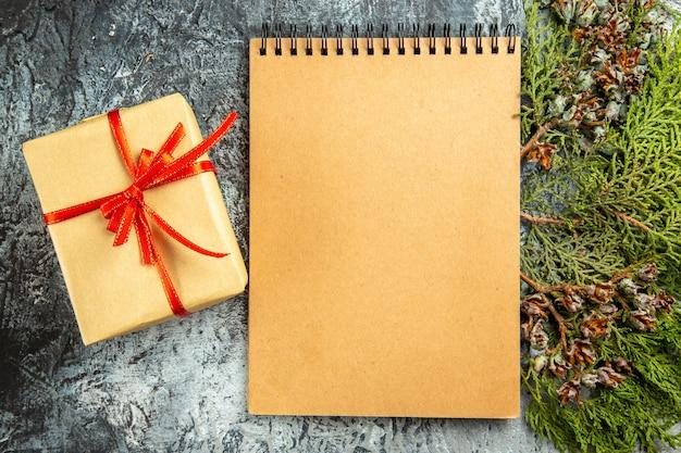 Presente pequeno amarrado com fita vermelha no bloco de notas ramo de pinho na superfície cinza.