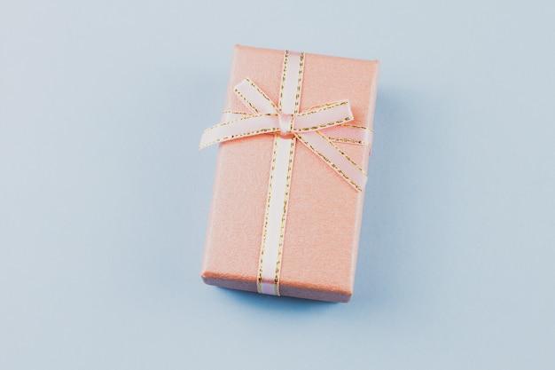 Presente pequeno em um fundo pastel, close up. caixa de presente com um laço