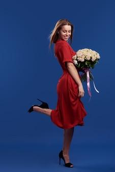 Presente perfeito. flores maravilhosas no dia das mulheres. concurso mulher morena sorridente segurando na frente do rosto o buquê de flores da primavera