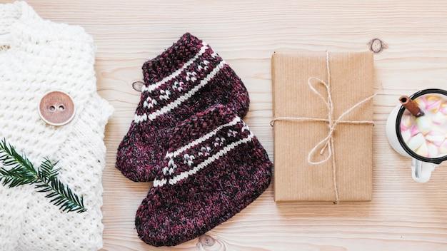 Presente perto de roupas quentes e chocolate quente