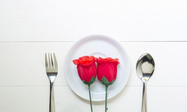 Presente presente com flor rosa vermelha e prato e colher e garfo na mesa de madeira