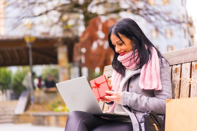 Presente surpresa, menina morena caucasiana abrindo o presente do namorado em uma videochamada com o computador, separados por distância
