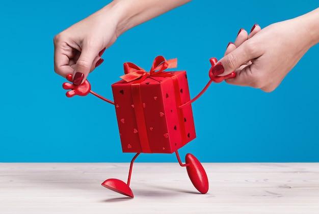 Presente. uma caixa em degraus de embalagem vermelha com pernas, segurando as mãos da mulher.