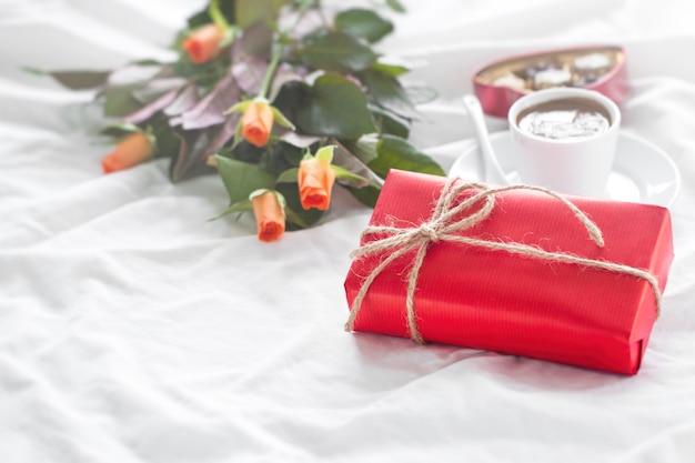 Presente vermelho com chocolates, um copo de café e flores