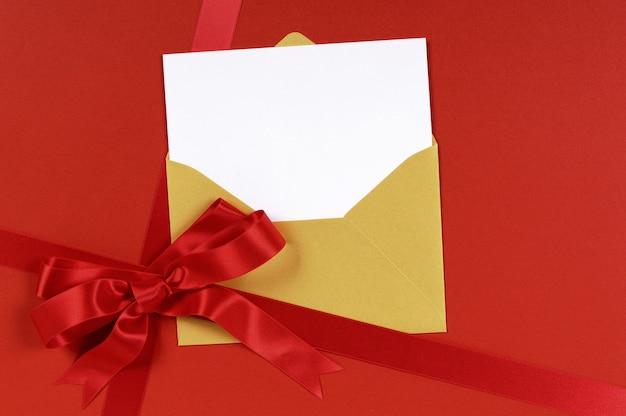 Presente vermelho com envelope ouro e convite em branco ou cartão de cumprimentos.