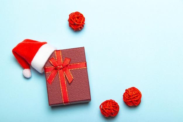 Presente vermelho sobre fundo azul. um presente com um chapéu de papai noel. natal e ano novo. um presente para o feriado. papel de embrulho vermelho. fundo azul