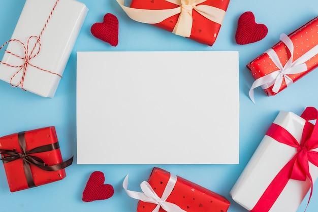 Presentes adoráveis e corações de malha em torno da folha de papel