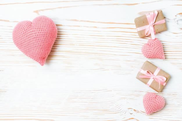 Presentes amarrados com uma fita rosa e corações de malha em uma madeira branca, vista superior
