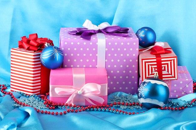 Presentes coloridos com bolas de natal azuis, flocos de neve e miçangas em fundo azul