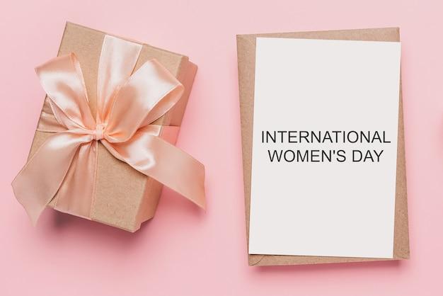 Presentes com carta de nota sobre fundo rosa isolado, conceito de amor e dia dos namorados com o texto dia internacional da mulher